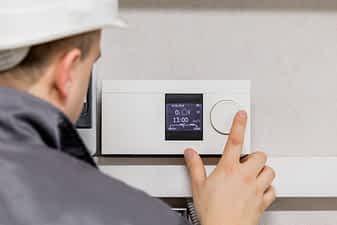 Technician adjusting Thermostat